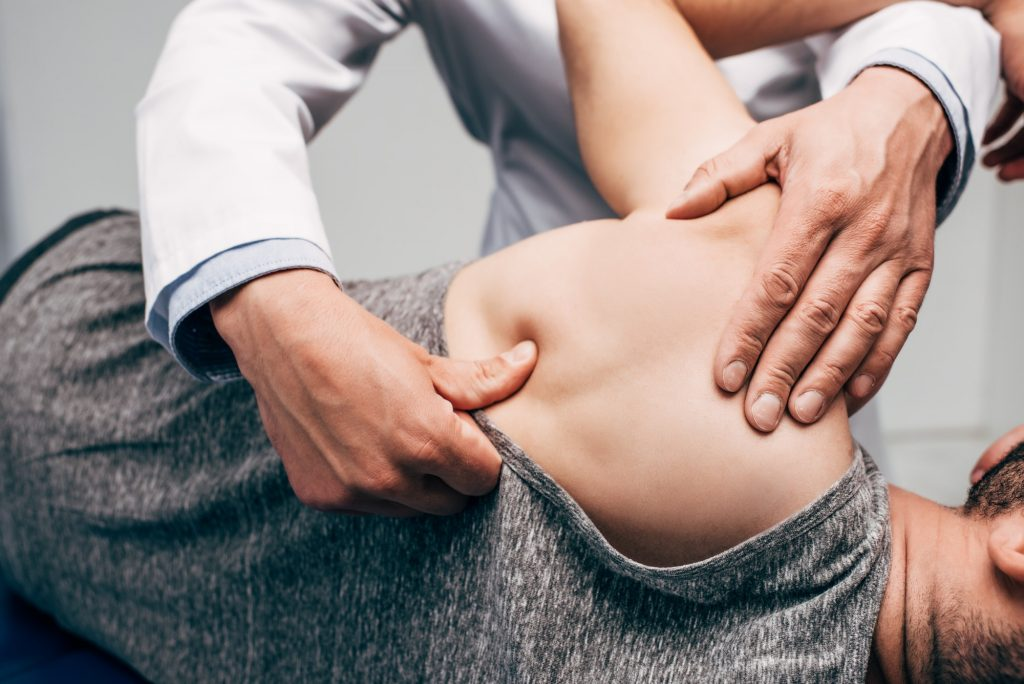 croped view of chiropractor massaging shoulder of man in hospital